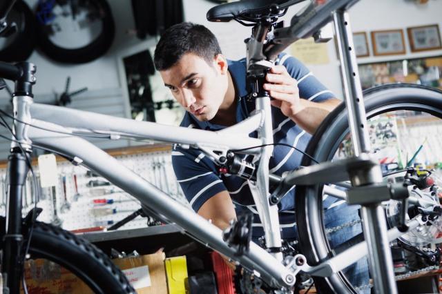 Man repairing bike in bike shop --- Image by © Stewart Cohen/Pam Ostrow/Blend Images/Corbis